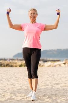 Vooraanzicht van oudere vrouw die gewichten steunt tijdens het trainen