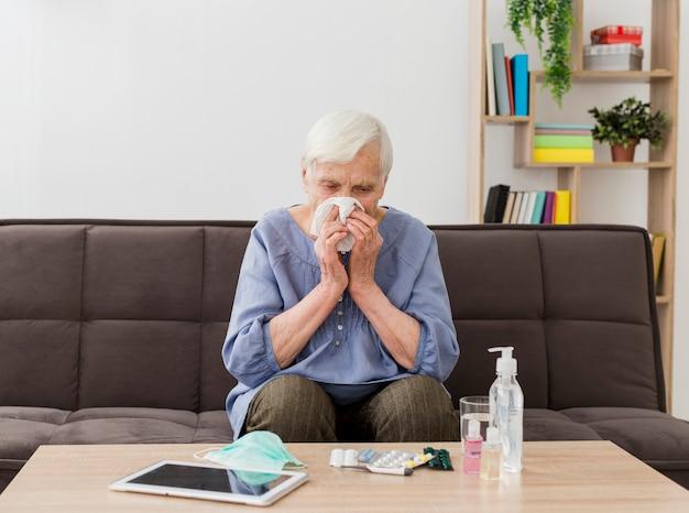 Vooraanzicht van oudere vrouw die haar neus in servet blaast