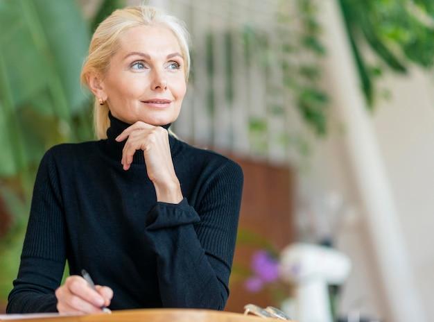Vooraanzicht van oudere vrouw die met pen werkt