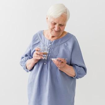 Vooraanzicht van oudere vrouw die thermometer bekijkt