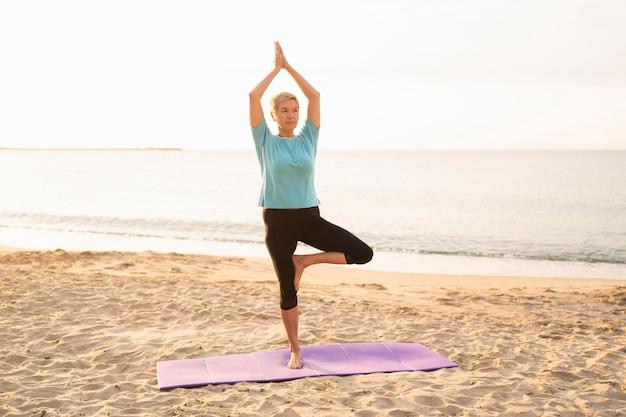 Vooraanzicht van oudere vrouw die yoga op het strand doet