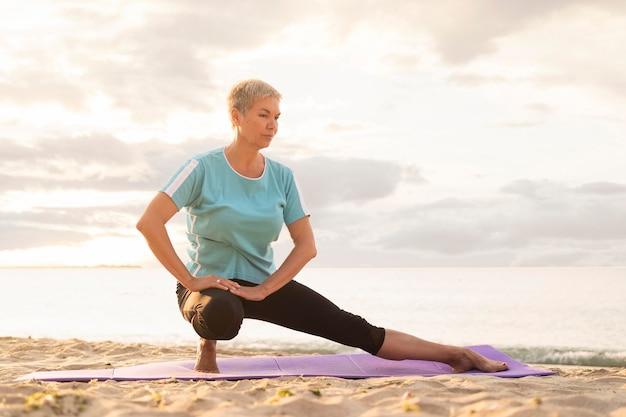 Vooraanzicht van oudere vrouw die yoga op strand beoefent
