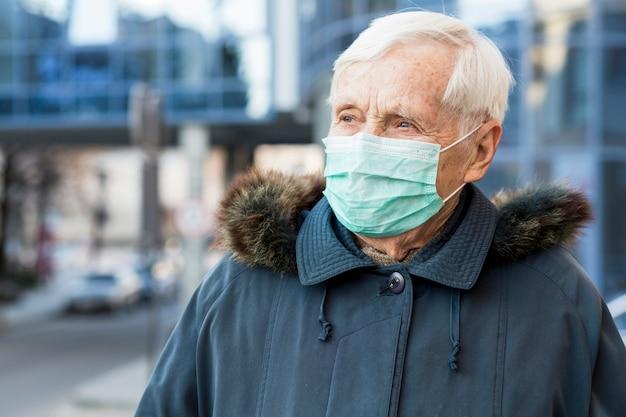 Vooraanzicht van oudere vrouw in de stad met een medisch masker