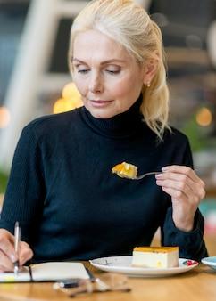 Vooraanzicht van oudere vrouw met dessert tijdens het werken