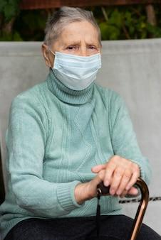 Vooraanzicht van oudere vrouw met medisch masker en stok bij verpleeghuis
