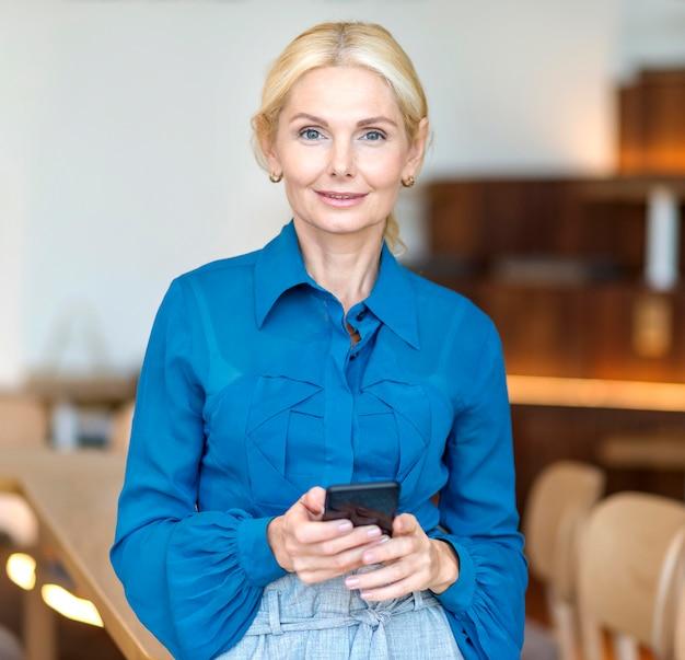 Vooraanzicht van oudere zakenvrouw werken en poseren met smartphone
