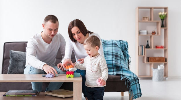 Vooraanzicht van ouders en kind thuis spelen