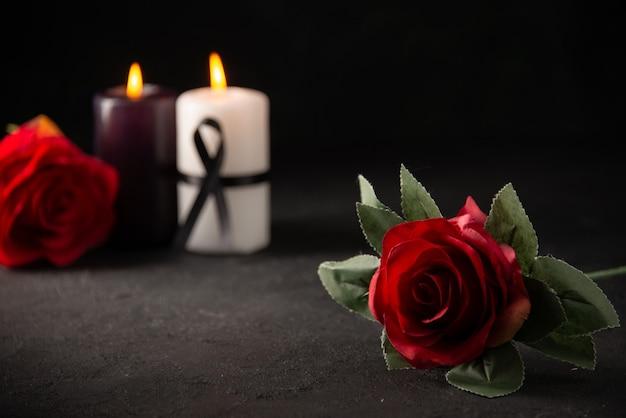 Vooraanzicht van paar kaarsen met rode bloemen op zwart