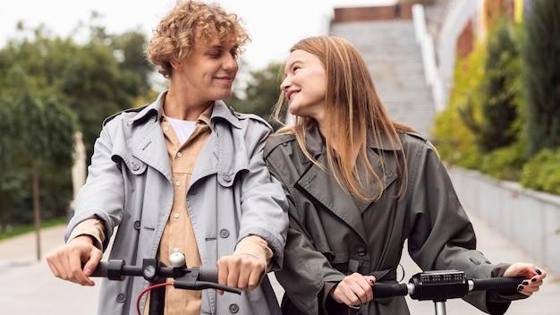 Vooraanzicht van paar met behulp van elektrische scooter buitenshuis