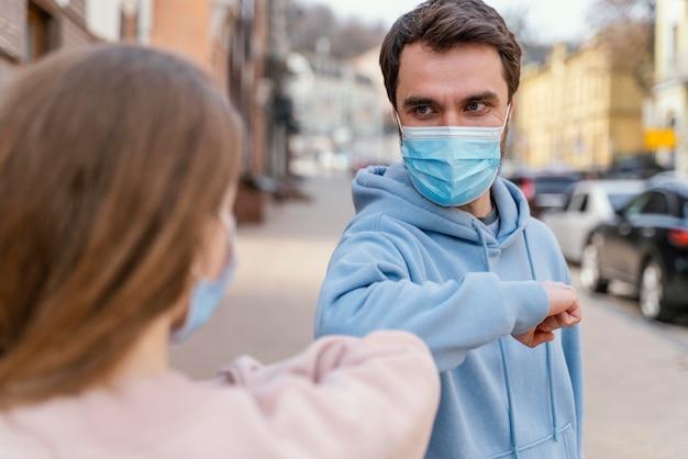 Vooraanzicht van paar met medisch masker met behulp van de elleboogbegroeting