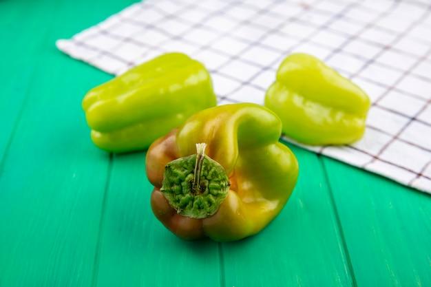 Vooraanzicht van paprika's op plaid doek en groen oppervlak