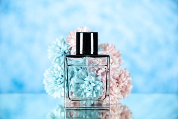 Vooraanzicht van parfumfles en bloemen op lichtblauwe vage vrije ruimte als achtergrond