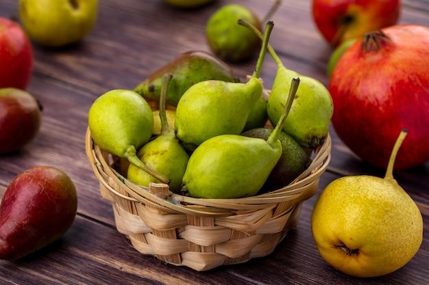 Vooraanzicht van perziken in mand met andere en appels granaatappel op houten oppervlak
