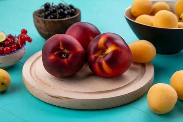 Vooraanzicht van perziken op een stand met rode en zwarte bessen en met abrikozen op een blauwe ondergrond