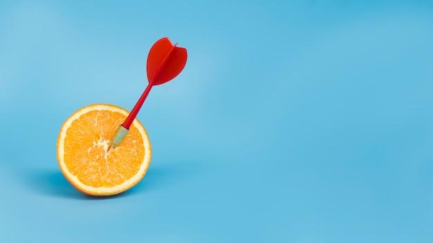 Vooraanzicht van pijltje dat in sinaasappel met exemplaarruimte wordt geplakt