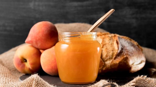 Vooraanzicht van pot met perzik jam en brood