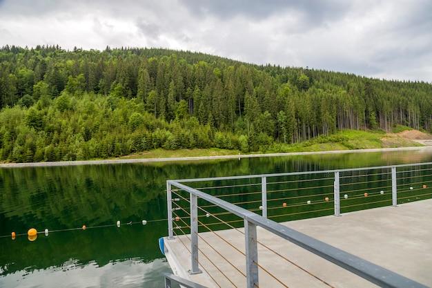 Vooraanzicht van prachtig groot meer en ongelooflijke groene bomen in het bos. concept van prachtige landschapsaard.