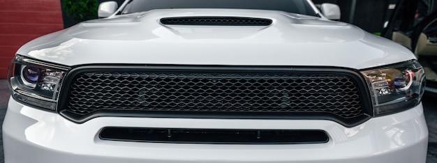 Vooraanzicht van prestigieuze auto in witte kleur close-up close-up van koplampen van een moderne suv-autobanner