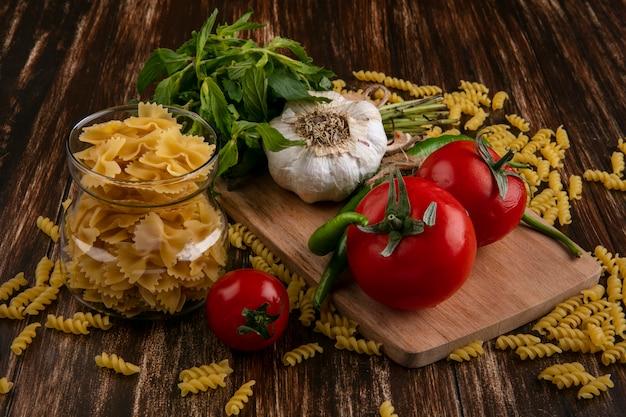 Vooraanzicht van rauwe pasta in een pot met tomaten, knoflook en chilipepers op een snijplank en met een bosje munt op een houten oppervlak