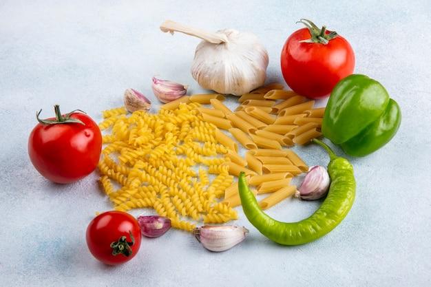 Vooraanzicht van rauwe pasta met bulgaarse tomaten en chilipepers en knoflook op een grijze ondergrond