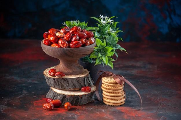 Vooraanzicht van rauwe zilverbessenvruchten binnen en buiten een kom op houten planken gestapelde koekjes en bloempot op de achtergrond van mixkleuren