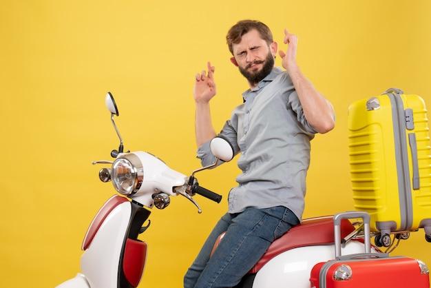 Vooraanzicht van reisconcept met bebaarde jongeman zittend op moto met koffers dromen door kruising vingers sluiten ogen erop op geel