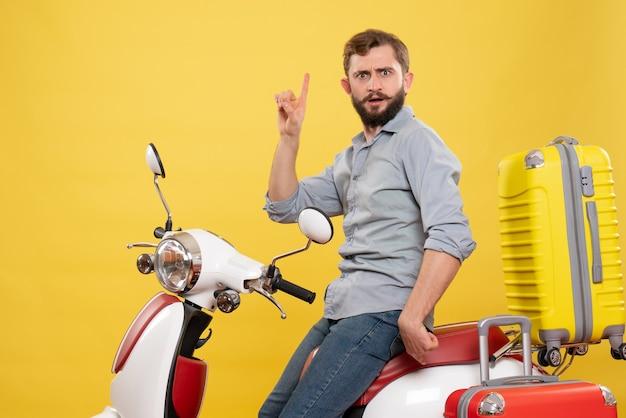 Vooraanzicht van reisconcept met denkende jongeman zittend op moto met koffers erop die op geel wijst