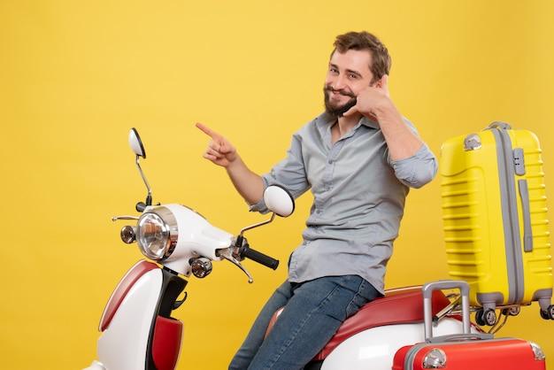 Vooraanzicht van reisconcept met lachende jonge man zittend op moto met koffers erop bellen me gebaar op geel