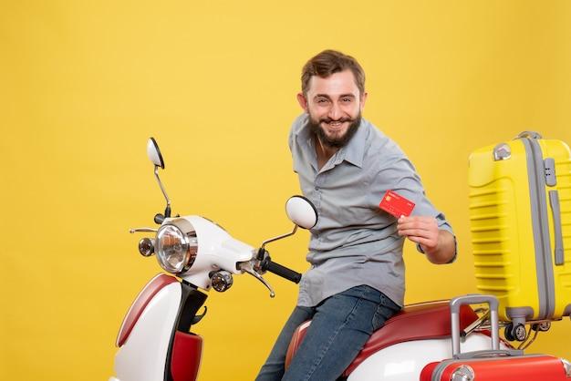Vooraanzicht van reisconcept met lachende jonge man zittend op moto met koffers met bankkaart erop op geel