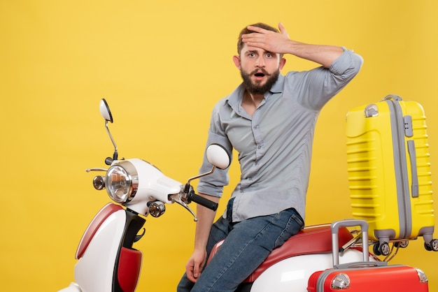 Vooraanzicht van reisconcept met uitgeputte jongeman zittend op moto met koffers erop op geel