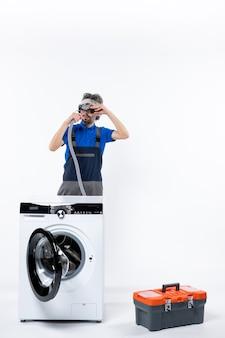 Vooraanzicht van reparateur in uniform staande achter wasmachine met koplamp die pijp op witte muur controleert