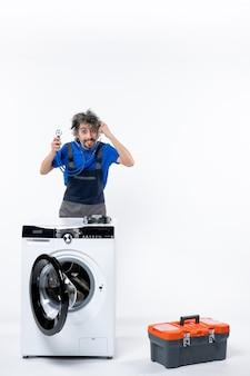 Vooraanzicht van reparateur met behulp van stethoscoop staande achter wasmachine op witte muur