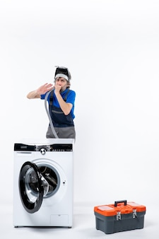 Vooraanzicht van reparateur met koplamp die achter wasmachine staat die pijp op witte muur uitblaast