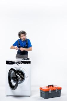 Vooraanzicht van reparateur met stethoscoop die zich achter wasmachine op witte muur bevindt