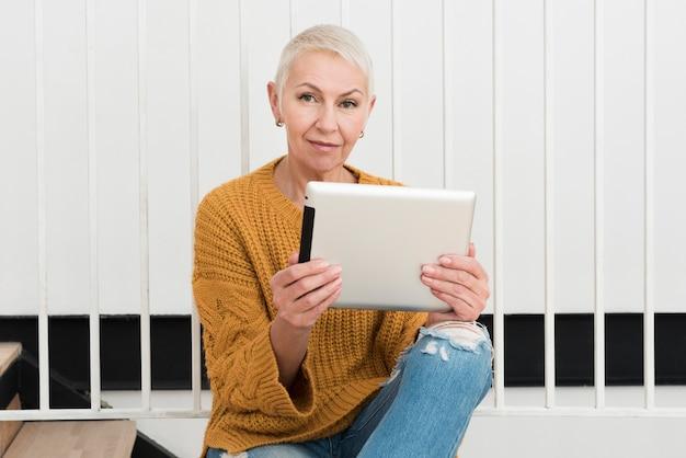 Vooraanzicht van rijpe vrouw die en tablet glimlachen houden