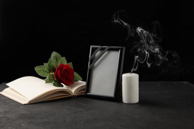 Vooraanzicht van rode roos met boek en fotolijst op zwart