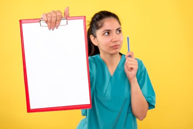 Vooraanzicht van rood klembord in vrouwelijke hand op gele geïsoleerde muur