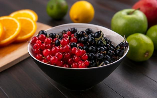Vooraanzicht van rood met zwarte bessen met appels op een houten oppervlak