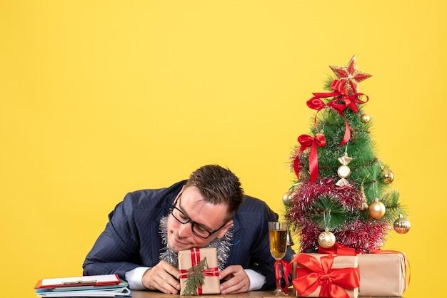 Vooraanzicht van rustgevende man hoofd zetten geschenkdoos zittend aan tafel in de buurt van kerstboom en presenteert op geel