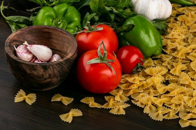 Vooraanzicht van ruwe deegwaren met tomatenknoflook en bulgaarse en spaanse peperpeper en munt