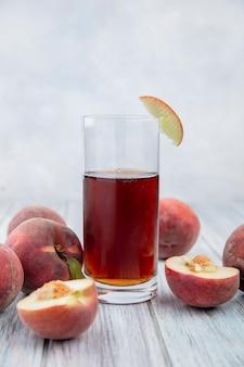 Vooraanzicht van sap in een glas met verse en heerlijke vruchten zoals appel perzik op wit oppervlak