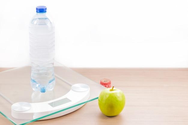 Vooraanzicht van schaal op houten tafel met fles water, meetlint, appel en witte achtergrond.