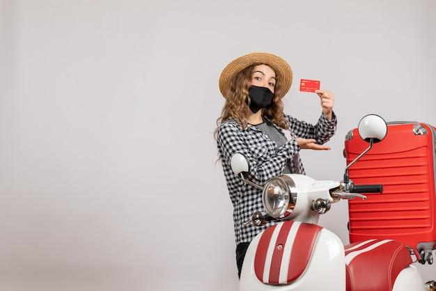 Vooraanzicht van schattig jong meisje met zwart masker houden reisticket staande in de buurt van rode bromfiets