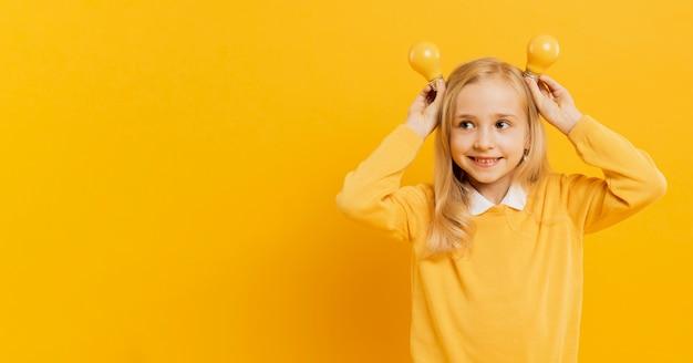 Vooraanzicht van schattig meisje poseren terwijl gele gloeilampen