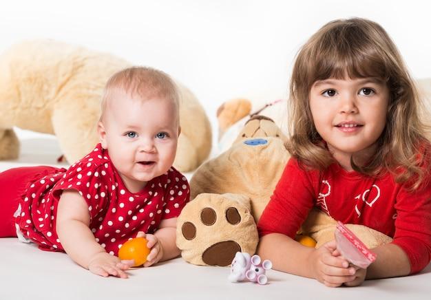 Vooraanzicht van schattige baby's liggend op de vloer met divers speelgoed.