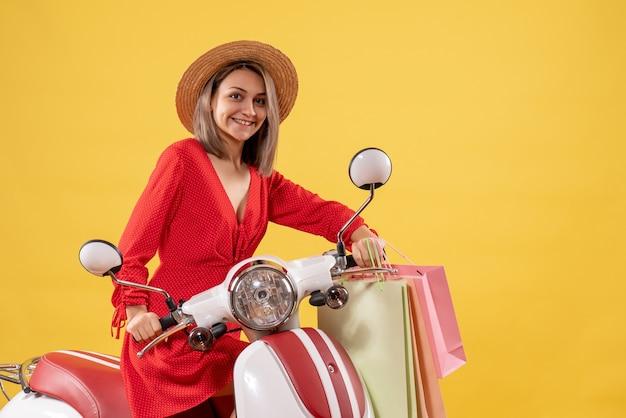 Vooraanzicht van schattige jonge vrouw in rode jurk op bromfiets met boodschappentassen