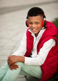 Vooraanzicht van schattige jongen, luisteren naar muziek