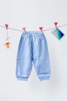 Vooraanzicht van schattige kleine babybroeken en accessoires