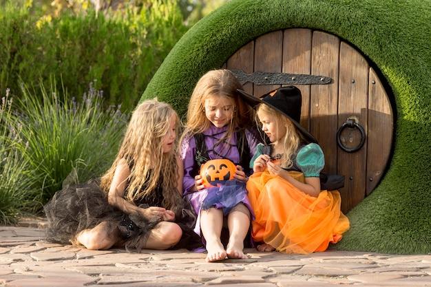 Vooraanzicht van schattige kleine meisjes met halloween-kostuums