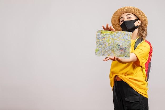 Vooraanzicht van schattige vrouwelijke reiziger die met rugzak kaart op witte muur steunt